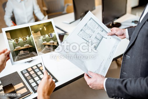 Creative office employees working on some architectural project, holding plans and interior renderings, close-up on the blueprints