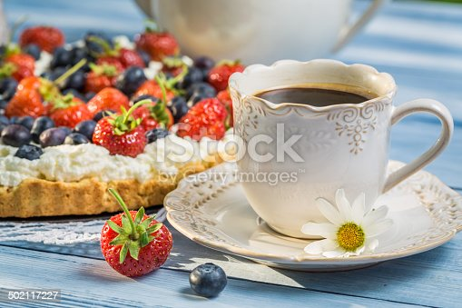 502634476 istock photo Close-up on coffee and tart with strawberries and blueberries 502117227