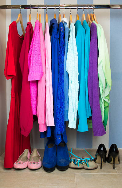 Closeup on color coordinated clothes on hangers stock photo
