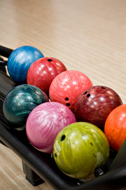 Close-up on colorful bowling balls in the ball return stock photo