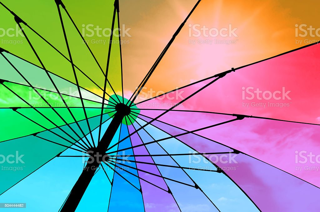 Closeup on colorful umbrella. See-through sky and sun. Abstract Color. stock photo