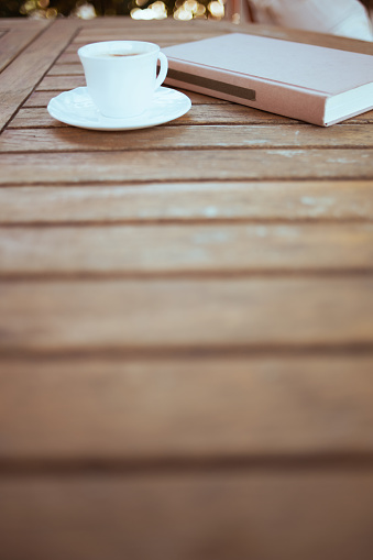 Closeup on cup of coffee and book at table in patio