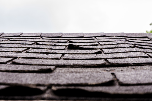 Close-up on damaged asphalt shingles over the roof of a shed in the backyard