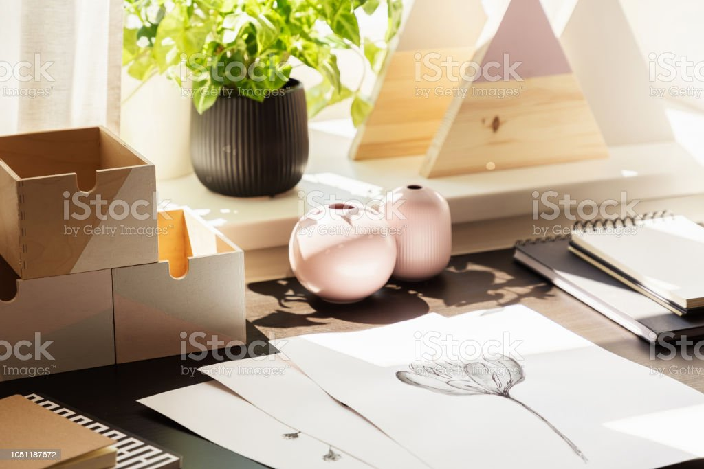 Close-up on desk with drawings and wooden boxes in workspace interior with plant. Real photo