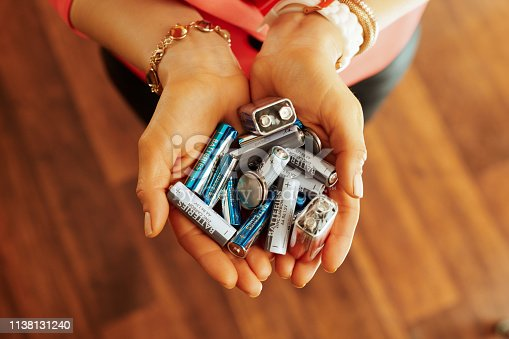 Closeup on different types of batteries in hand of modern housewife in the house.