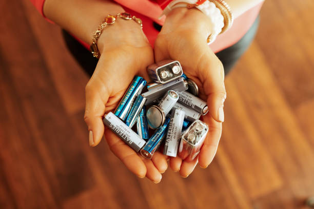 Closeup on different types of batteries in hand of housewife stock photo