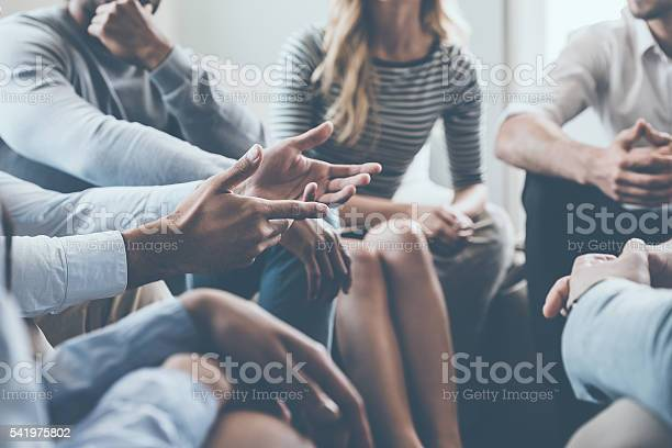 Close-up of people communicating while sitting in circle and gesturing