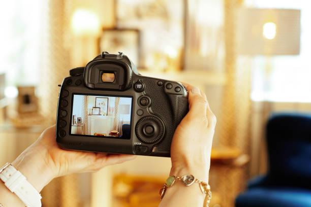 close-up op dslr camera in de hand van vrouwelijke interieur fotograaf - foto stockfoto's en -beelden