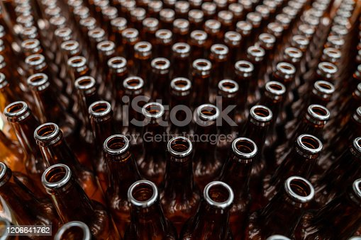 Close-up on empty bottles ready to be filled at a beer factory - industrial concepts