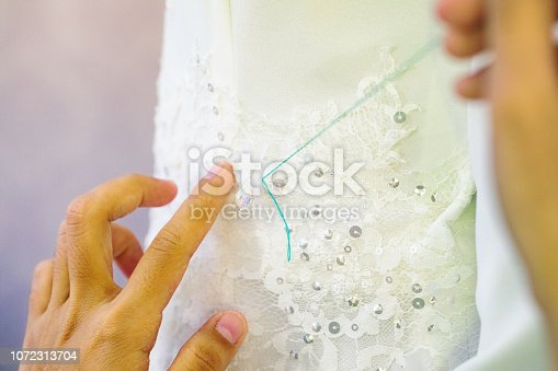 Close-up on female hands sewing wedding dress details.