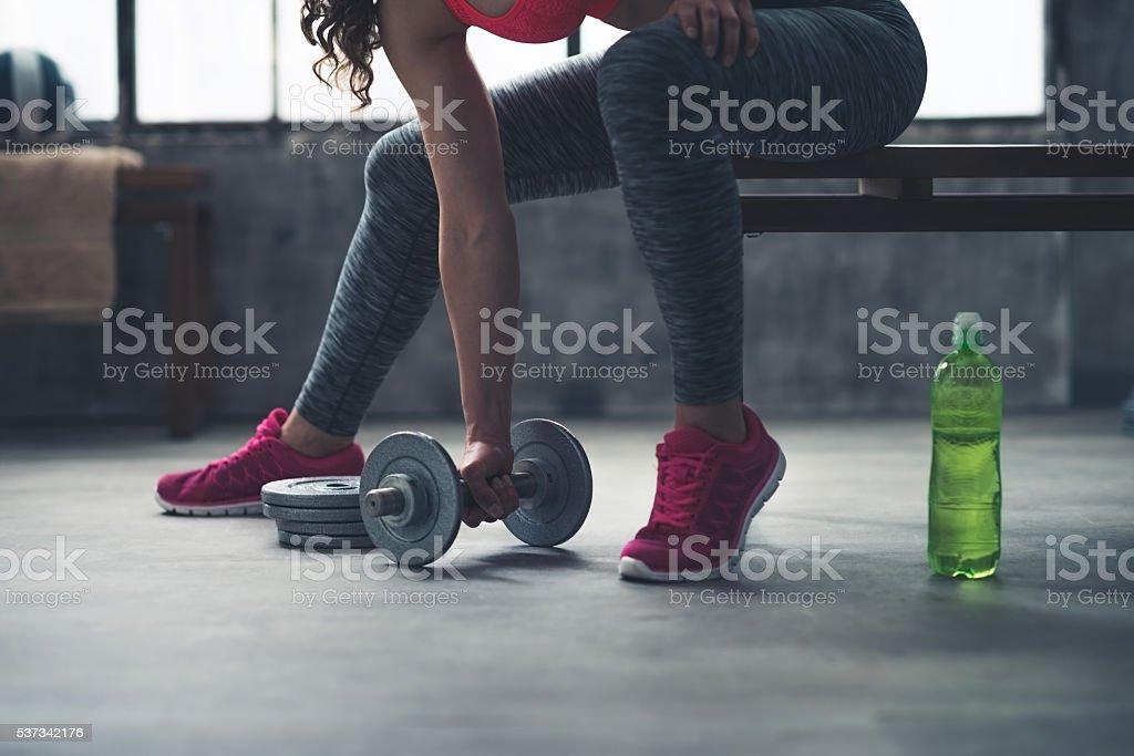 Nahaufnahme auf fitness Frau mit Hantel vom Boden im Fitnessraum – Foto