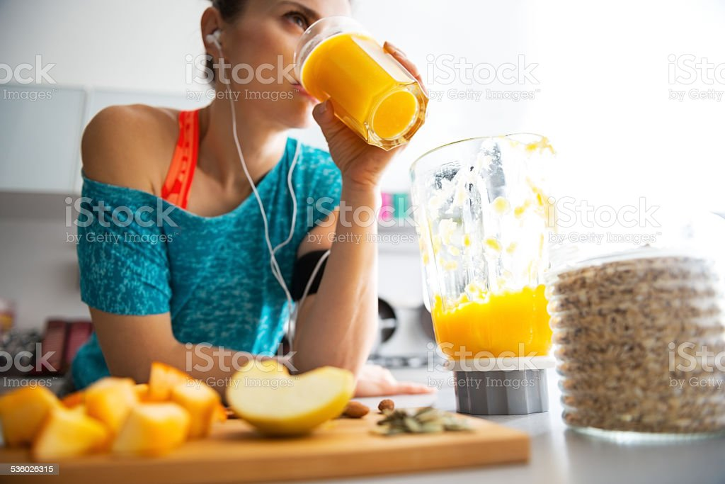 close-up on fitness young woman drinking pumpkin smoothie in kitchen stock photo