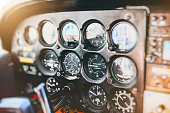 Vibrant color photography horizontal composition of close-up on several common flight instruments in old small propeller airplane cockpit interior without people in the frame, and selective focus on control panel dashboard.