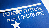 Close-up on French European Union constitution documents blue colored, selective focus on title on first page of the brochure with white color stars, placed on white table in studio.