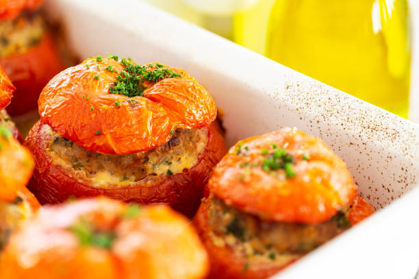 Close-up on French stuffed tomatoes with meat, bread crumbs, and herbs in a white dish, aside a bottle of olive oil. stock photo