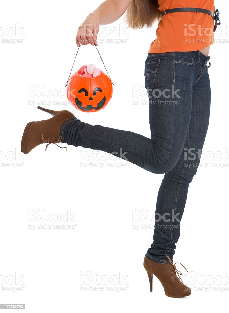 closeup on halloween bucket with sweets holding by woman stock photo