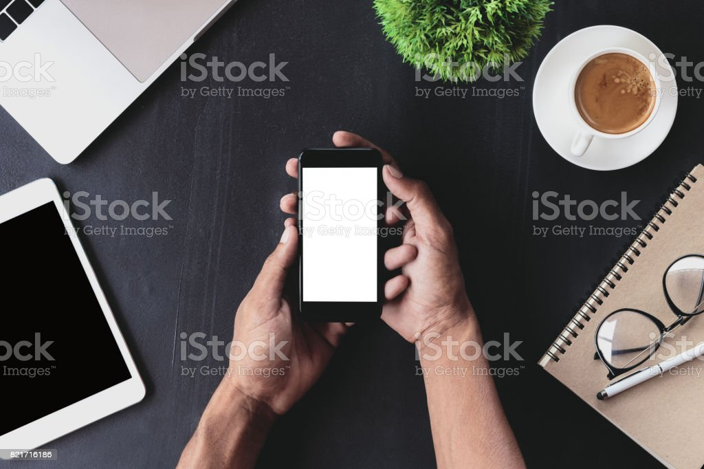 close-up on hand holding phone showing white screen on desk