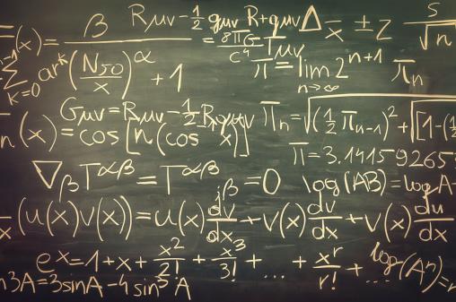Close-up on hand written mixed mathematical formulas, blackboard, retro look