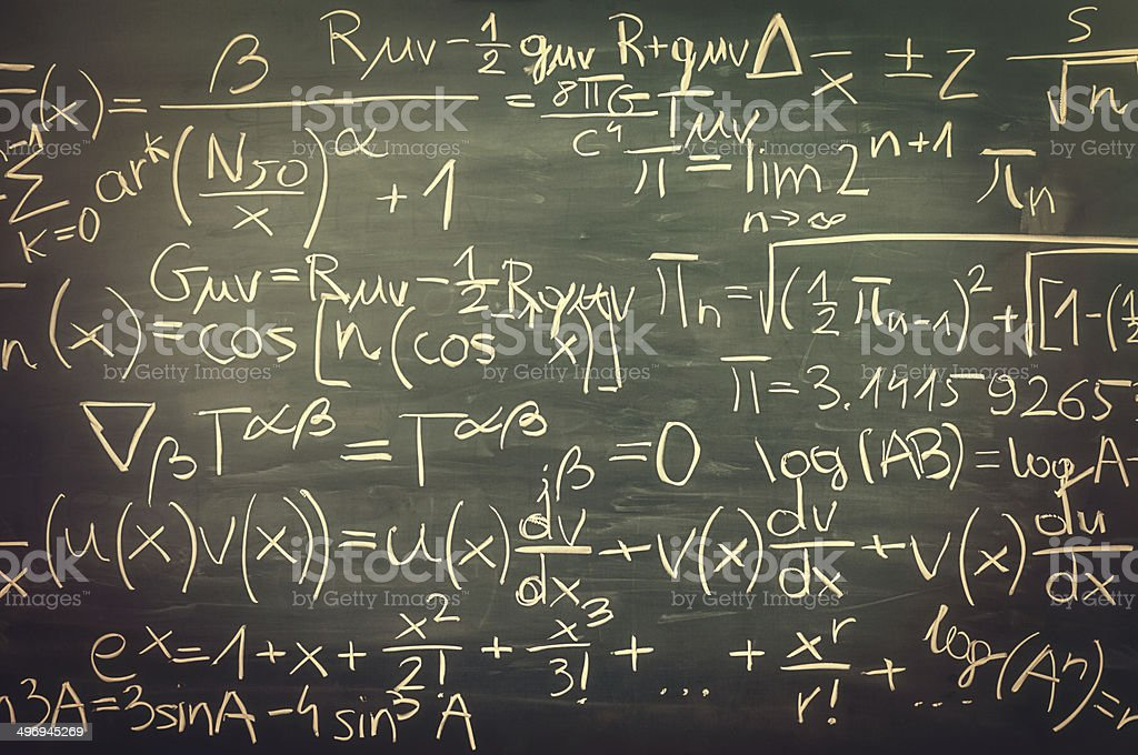 Close-up on hand written mixed mathematical formulas, blackboard, retro look stock photo