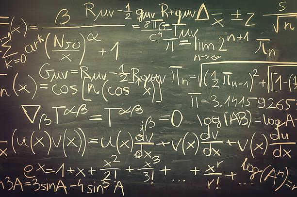 Close-up on hand written mixed mathematical formulas, blackboard, retro look stock photo