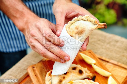 Close-up on onhands presenting an empanada tucumana wrapped in paper with more in the background.