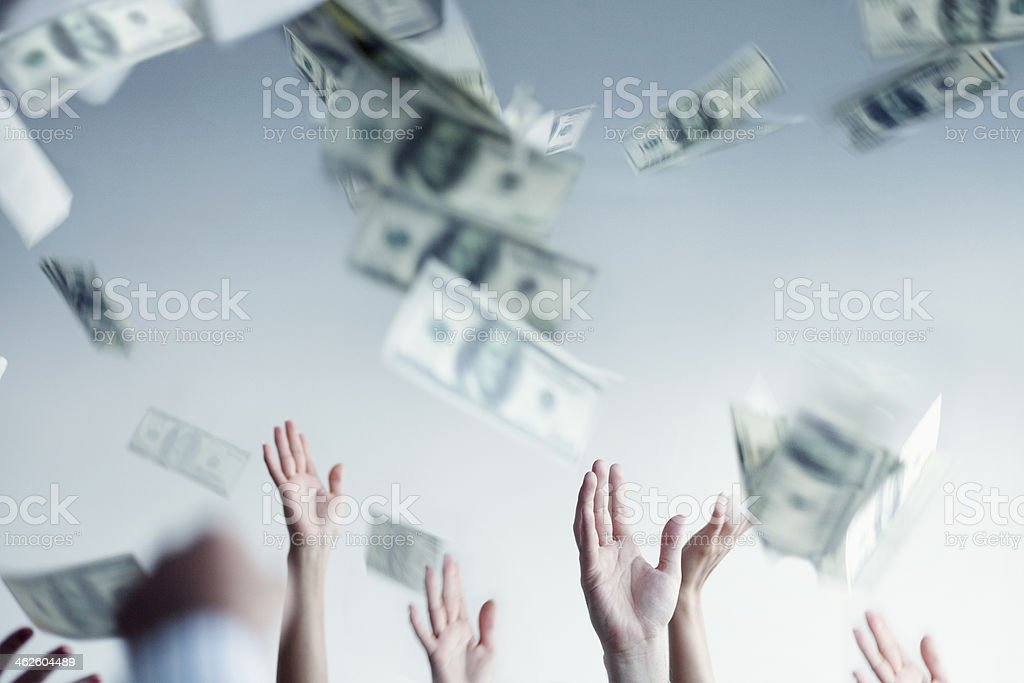 Close-up on hands raised throwing and catching money in air stock photo