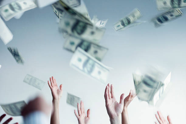 close-up on hands raised throwing and catching money in air - throw money away stock pictures, royalty-free photos & images