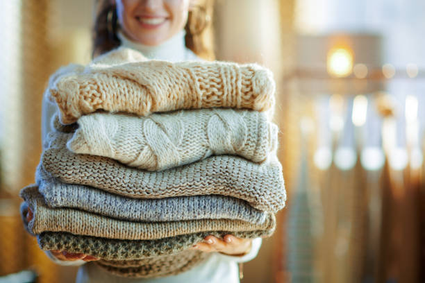 Closeup on happy elegant housewife holding pile of sweaters stock photo