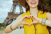 Closeup on happy modern traveller woman in yellow blouse and hat showing heart shaped hands against Eiffel tower in Paris, France.