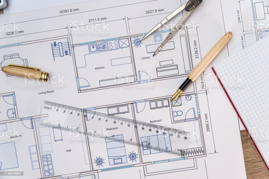 Close-up on house plan with ruler, pen and notebook