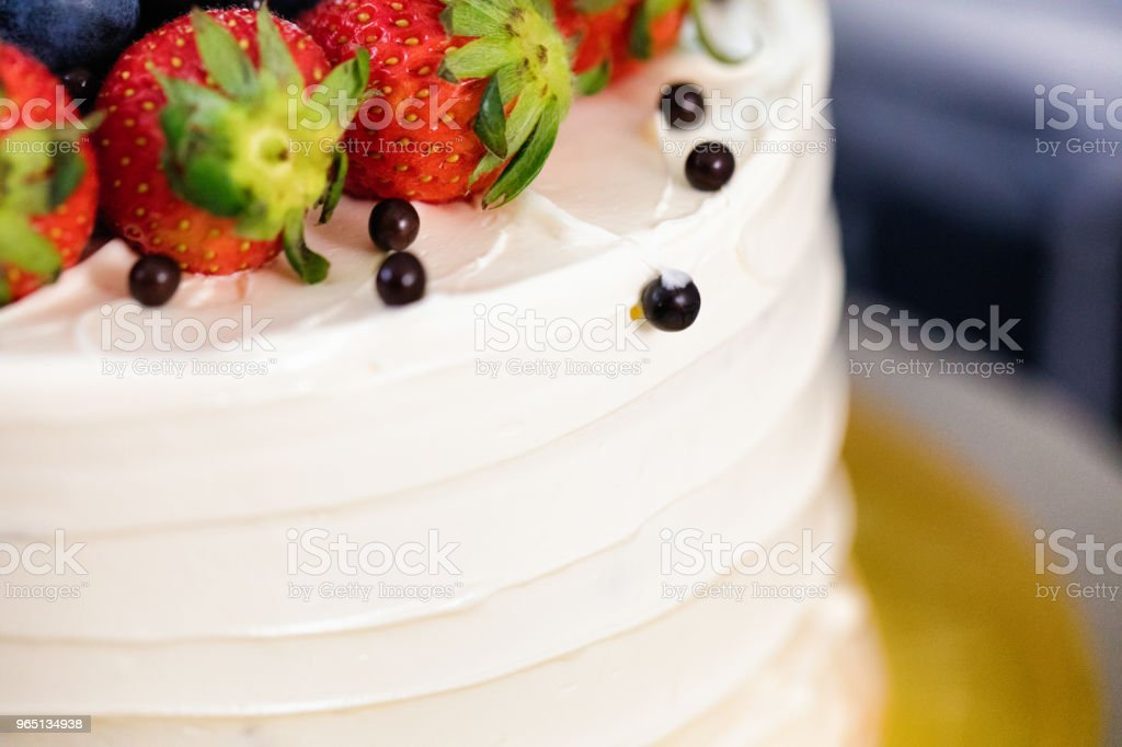 Close-up on iced layer cakes with berries on top royalty-free stock photo