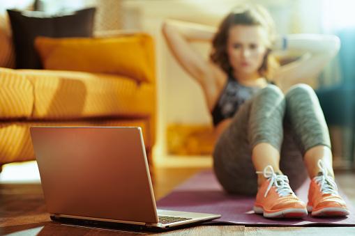 Closeup On Laptop And Woman Doing Abdominal Crunches - zdjęcia stockowe i więcej obrazów Aplikacja mobilna
