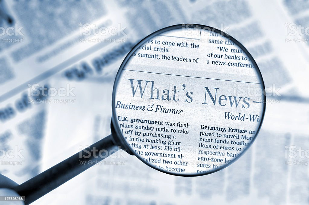 Close-up on magnifying glass above Wall Street Journal newspaper, blue royalty-free stock photo