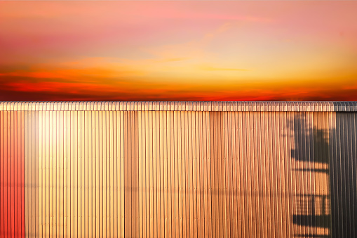 Closeup on metal sheet wall material with reflection of sunset at twilight time.