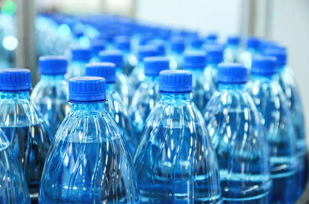closeup on mineral water bottles in raw and lines - plastic stock pictures, royalty-free photos & images