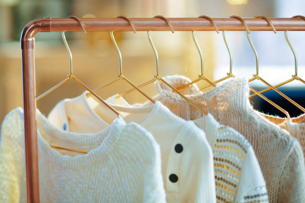 Closeup on modern copper clothes rack with sweaters on hangers stock photo