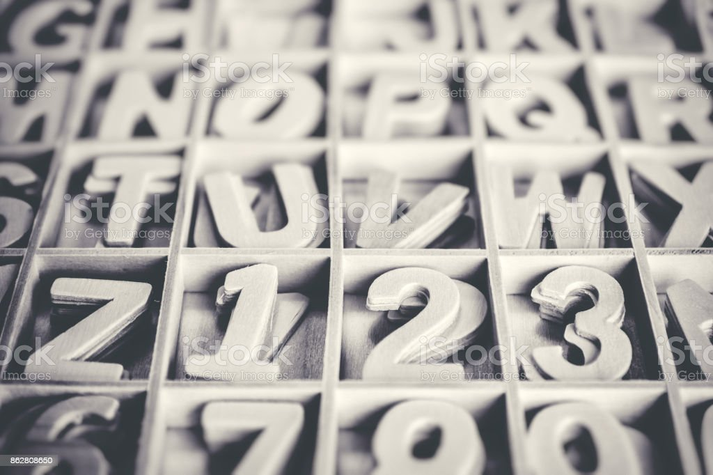 close up on multiple alphabet small wooden letters and numbers on dark gray texture royalty