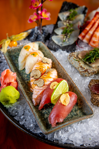 Close-up on nigiri with truffle garnish, ginger and wasabi on the side, serving dish full of ice with Japanese raw food delicacies