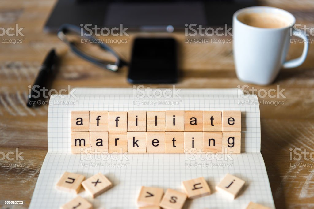Closeup on notebook over wood table background, focus on wooden blocks with letters making Affiliate Marketing words stock photo