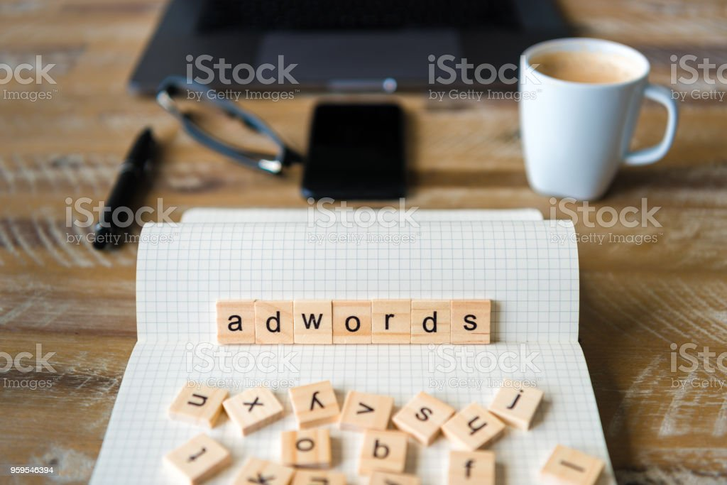 Closeup on notebook over wood table background, focus on wooden blocks with letters making Adwords word – zdjęcie