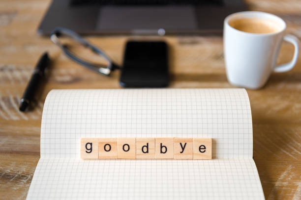 Closeup on notebook over wood table background, focus on wooden blocks with letters making Goodbye word Closeup on notebook over wood table background, focus on wooden blocks with letters making Goodbye word. Business concept image. Laptop, glasses, pen and mobile phone in a defocused background. apart stock pictures, royalty-free photos & images