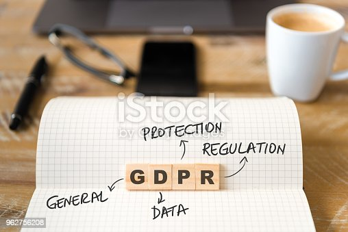 Closeup on notebook over wood table background, focus on wooden blocks with letters making GDPR General Data Protection Regulation text. Business concept image.