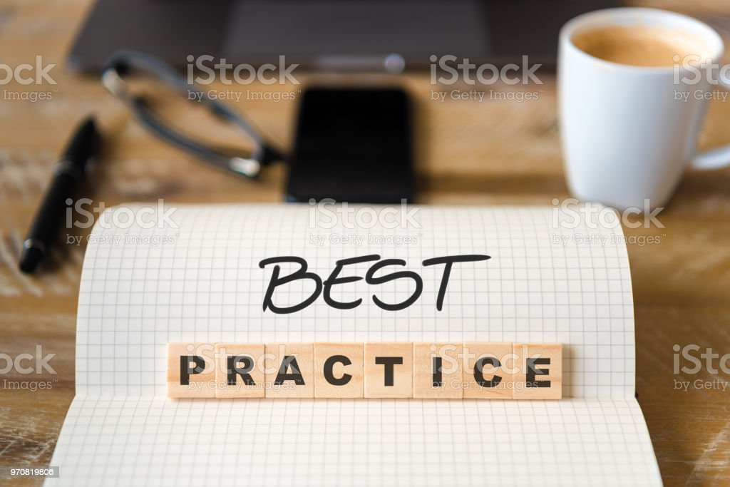 Closeup on notebook over wood table background, focus on wooden blocks with letters making Best Practice text stock photo