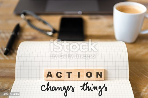 istock Closeup on notebook over wood table background, focus on wooden blocks with letters making Action Changes Things text 989180496