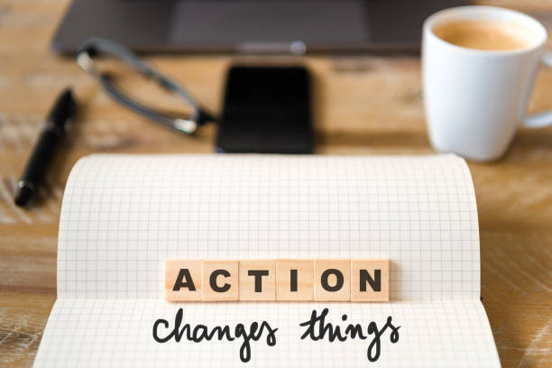 closeup on notebook over wood table background, focus on wooden blocks with letters making action changes things text - target australia stock pictures, royalty-free photos & images