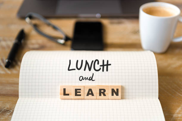 Closeup on notebook over wood table background, focus on wooden blocks with letters making Lunch and Learn text stock photo