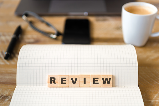1163501702 istock photo Closeup on notebook over wood table background, focus on wooden blocks with letters making Review text 989201948