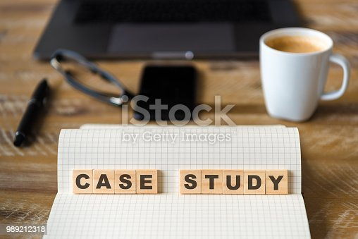 Closeup on notebook over wood table background, focus on wooden blocks with letters making Case Study text. Concept image. Laptop, glasses, pen and mobile phone in defocused background