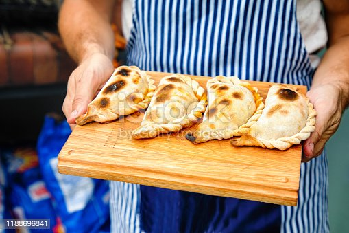 Close-up on perfectly baked empanadas tucumanas on a cutting board held by baker outdoors.