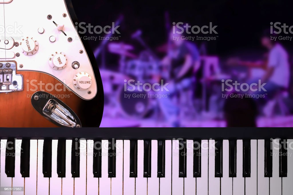 Closeup on piano and guitar with on stage concert background in ultra violet theme lighting background. - Royalty-free Arts Culture and Entertainment Stock Photo